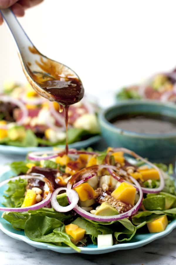 spoon drizzling tangy and salty dressing over a seared ahi tuna salad with avocado and mango