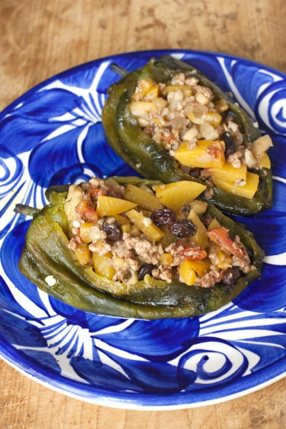 two chile poblanos stuffed with picadillo on a Mexican blue and white plate