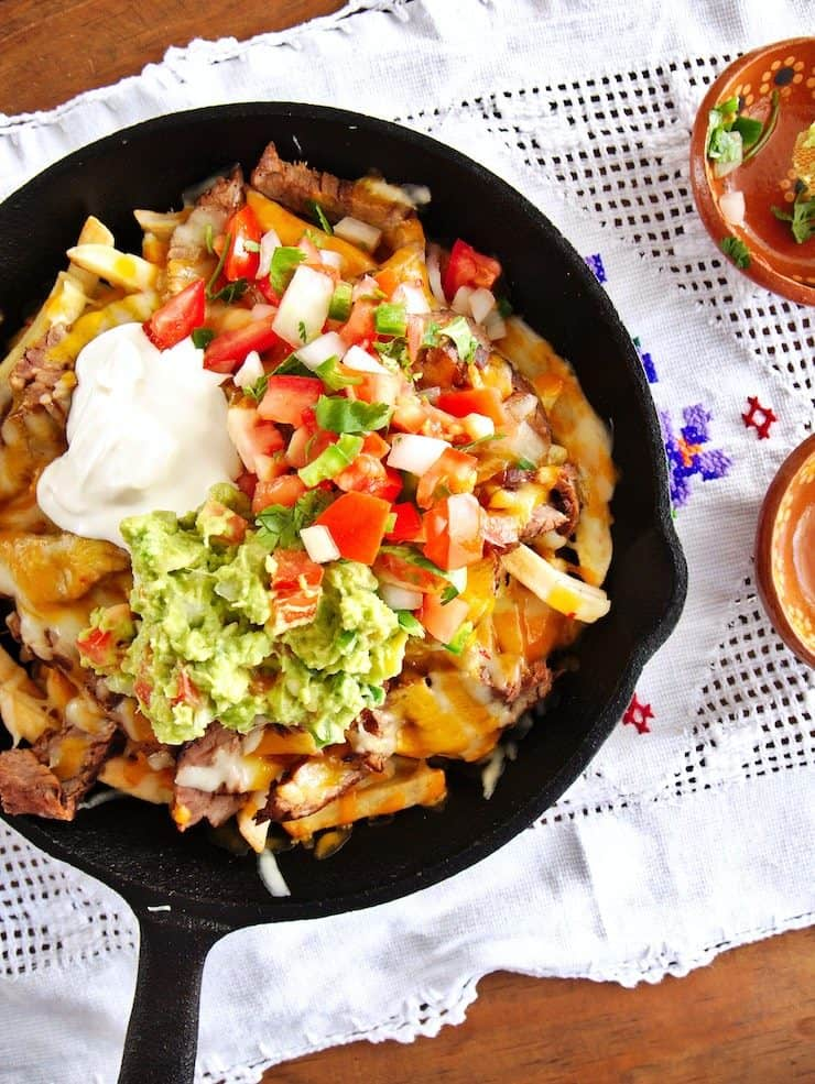Carne Asada fries in a skillet topped with sour cream guacamole and pico de gallo
