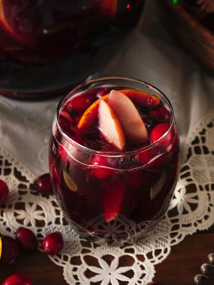 glass of red Christmas Sangria under white linen