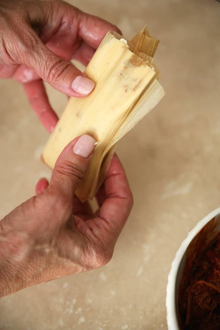 Tamal Dough (Masa para Tamales) hands holding a raw tamal