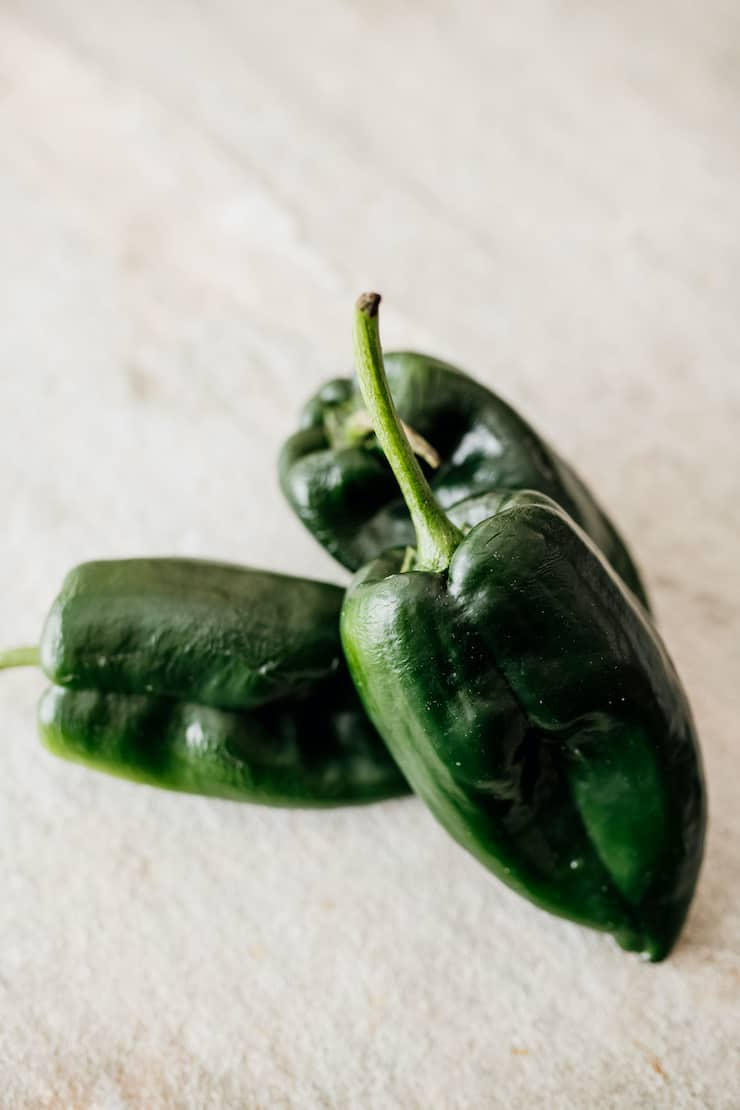three poblano Chile peppers on a white background
