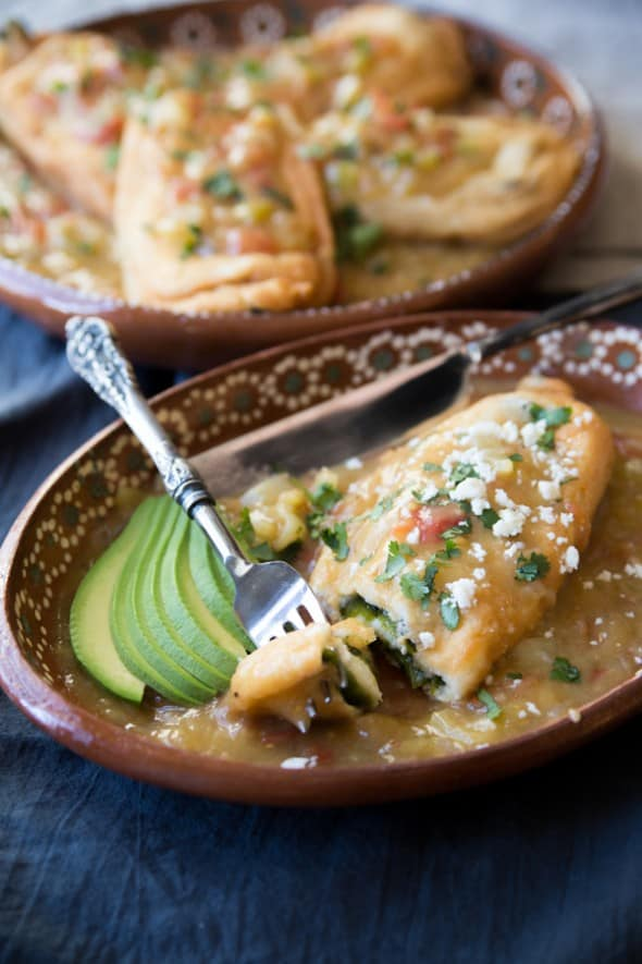 poblano Chiles Rellenos with a salsa on top with slices of avocado perfect for lent
