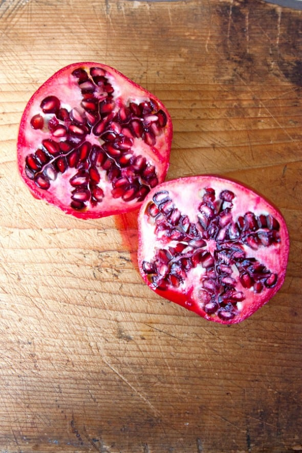 open pomegranate on a wooden cutting board