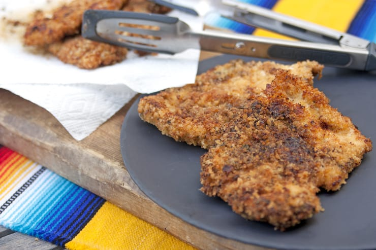 calphalon tongs and Milanesa breaded chicken on a platter