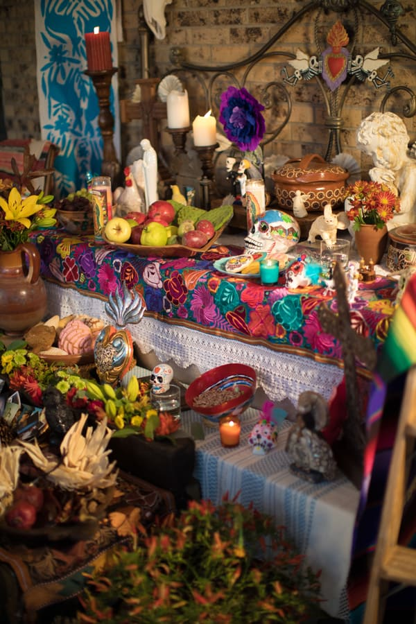 candles lit on altar for dia de los muertos