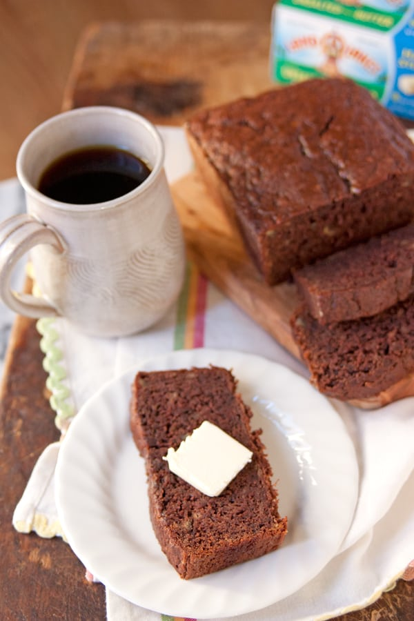 chocolate banana bread sliced with a pad of butter and served with coffee