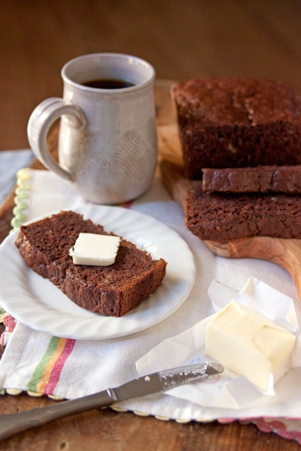 mexican chocolate banana bread sliced on a plate with a cup of coffee