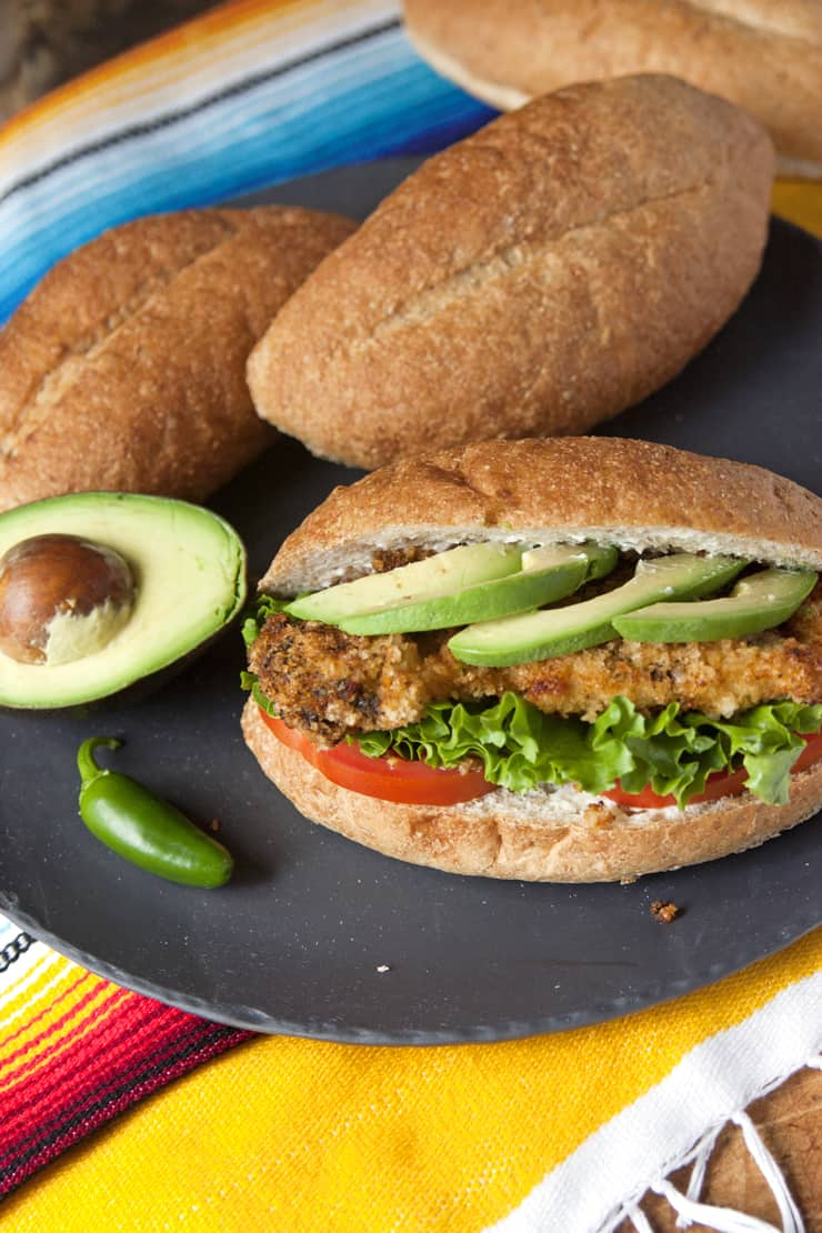black platter with a torta milanesa a bolillo with Milanesa breaded chicken with avocado slices tomato and lettuce and a half avocado on the side