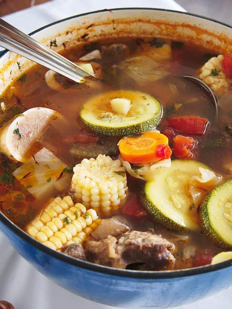 pot of caldo de res with corn zucchini and beef and bones