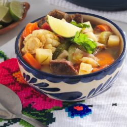 bowl of mexican vegetable beef soup in a white and blue painted ceramic bowl