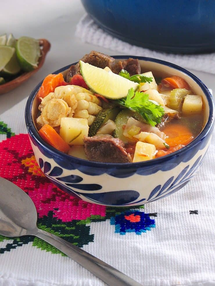 caldo de res beef soup in a Mexican blue and white bowl