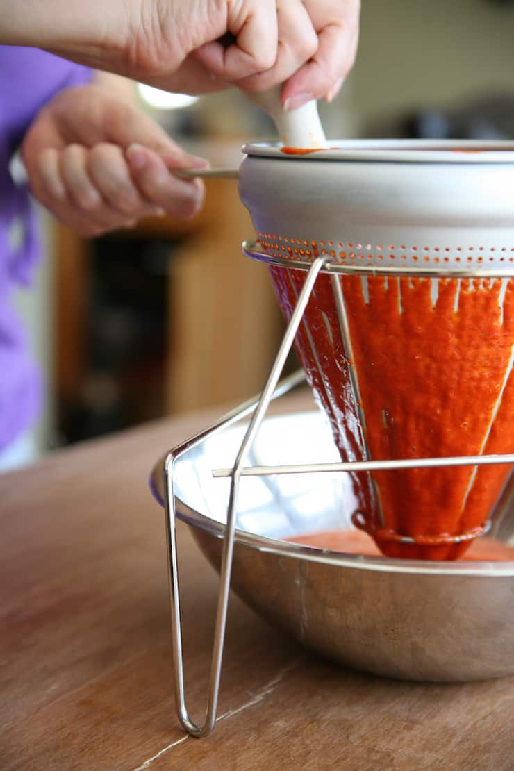 hands straining red chile enchilada sauce through a conical sieve or chinois