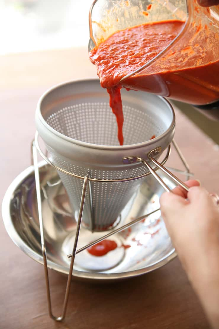 red chile sauce being poured from blender into a conical sieve