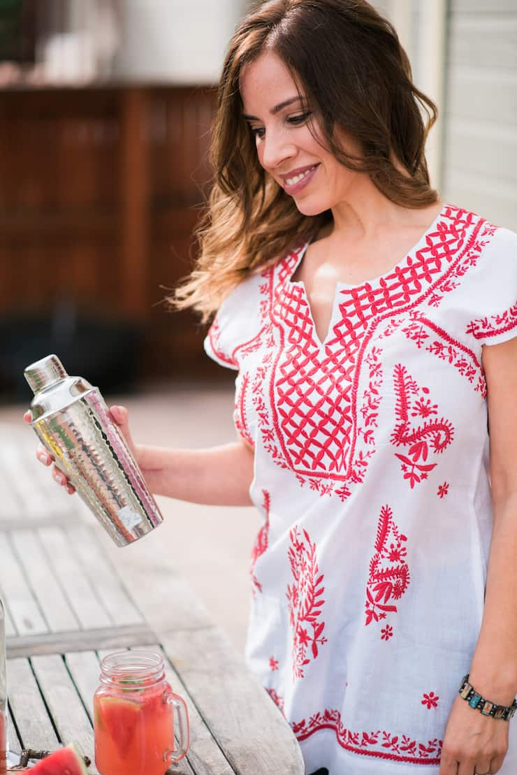Latina blogger Yvette from Muy Bueno Cookbook shaking a silver cocktail shaker with watermelon mexican mule