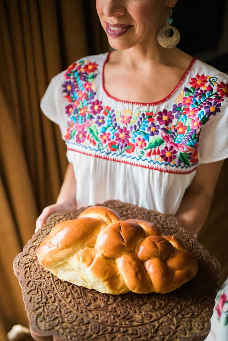 Holding a big loaf of the delicious challah bread on an incredible authentic board