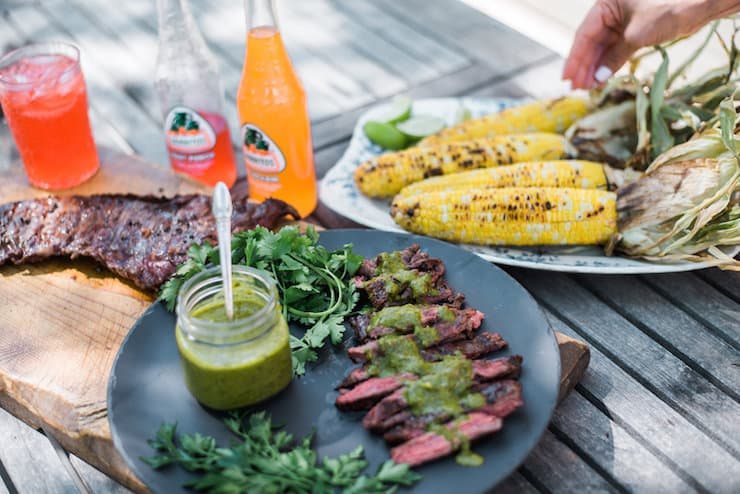 Adding grilled corn to the table served with Grilled Skirt Steak with Chimichurri Sauce and a big steak right next to the plate
