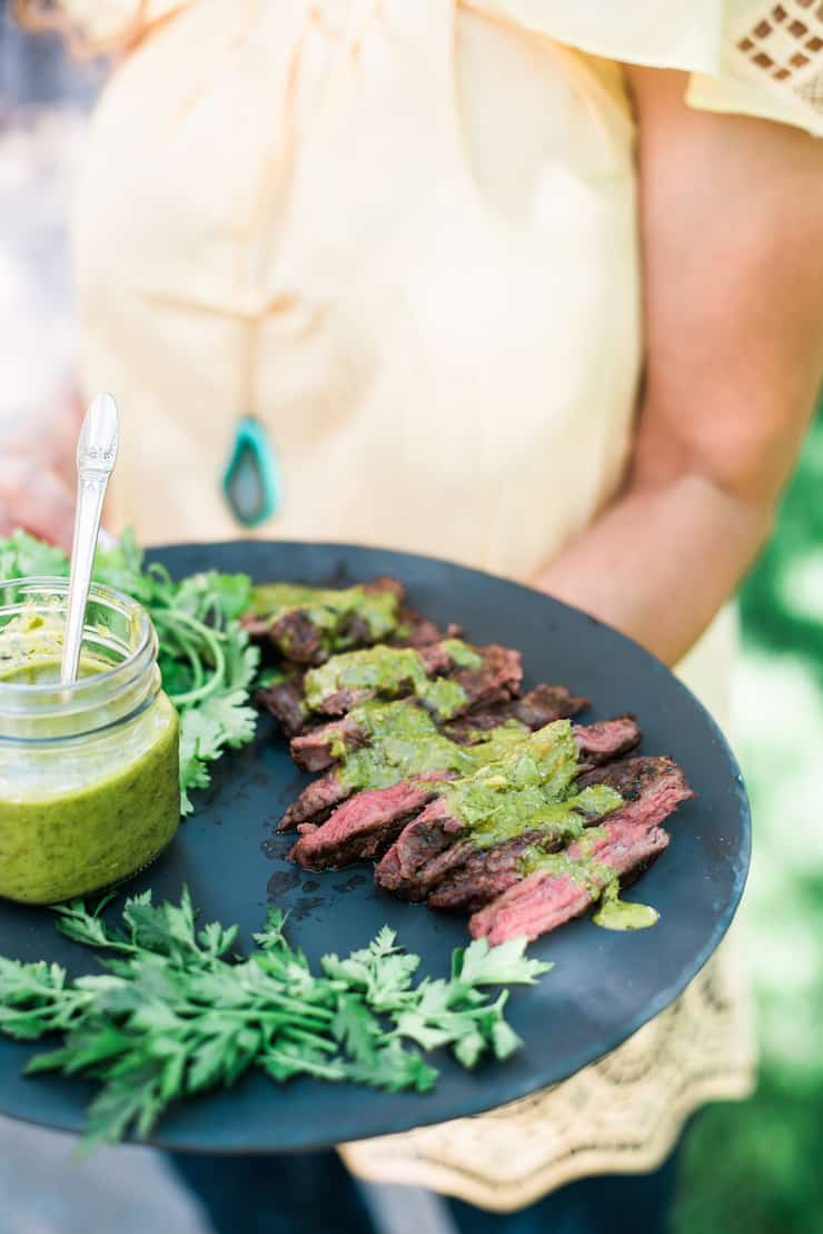 Serving Grilled Skirt Steak with Chimichurri Sauce on a big dark plate outside during a nice sunny day