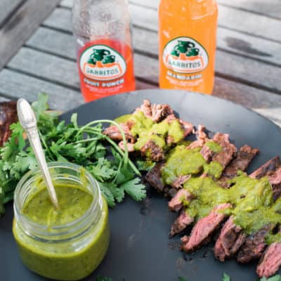Grilled Skirt Steak with Chimichurri Sauce with two bottles of Jarritos on a wooden table