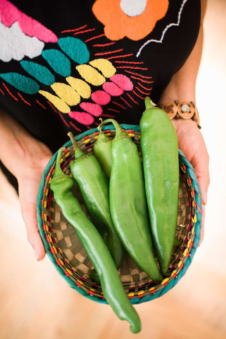 hands holding a basket with fresh Hatch Chile