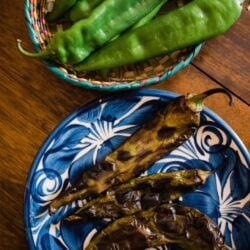 two earthenware bowls one filled with fresh hatch chiles, one filled with roasted chiles