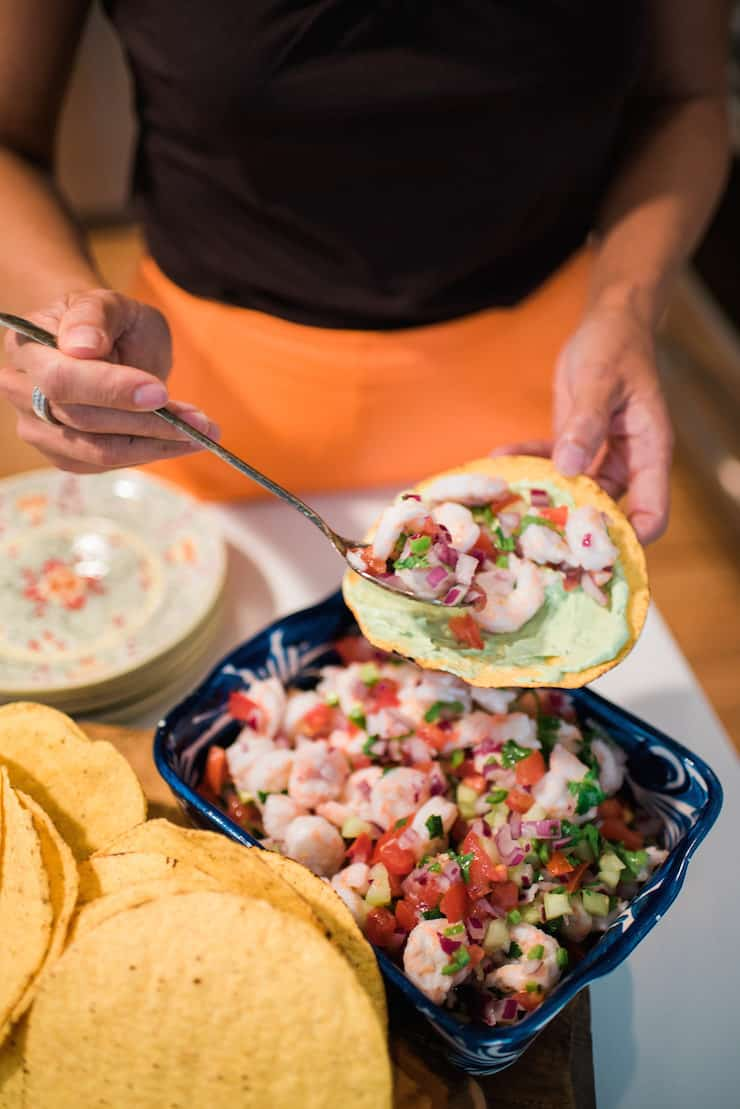 girl topping a tostada with Shrimp Ceviche (Ceviche de Camarón)