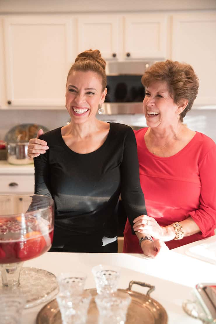Latina Mexican-American mother and daughter laughing in the kitchen during a tamalada