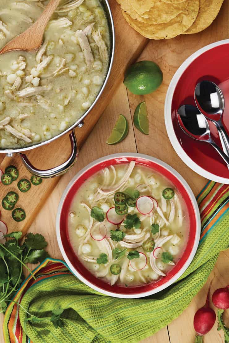 Bowl and pot filled with chicken pozole verde Mexican hominy stew