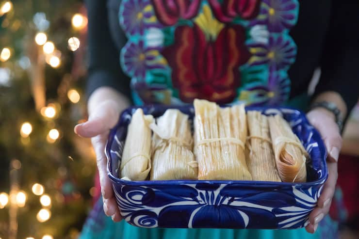 holding a blue and white platter of tamales
