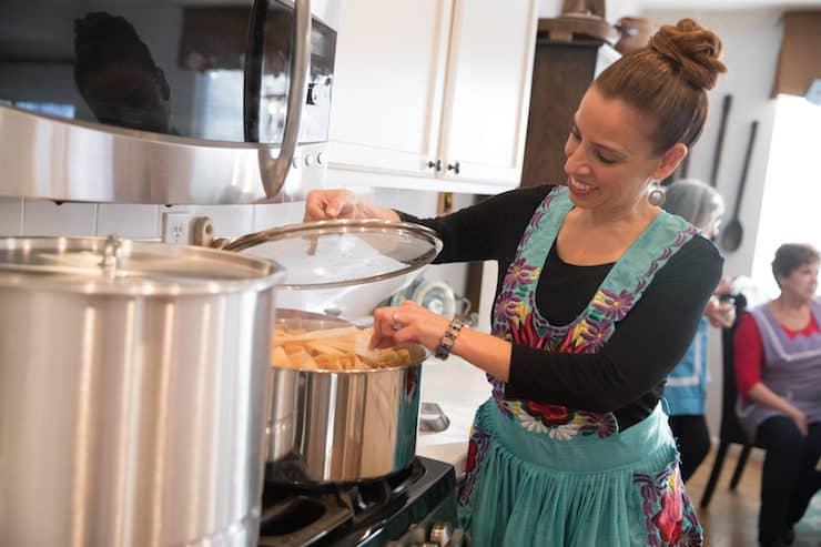 Latina mother wearing an apron making tamales at a tamalada
