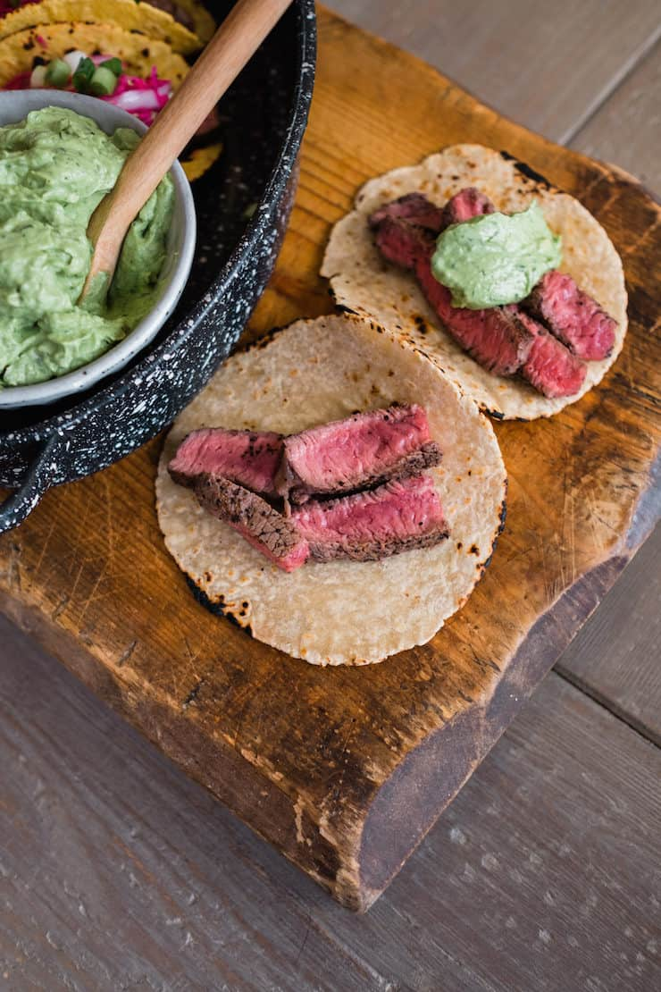 sliced bison steak on corn tortillas on a cutting board and topped with avocado crema