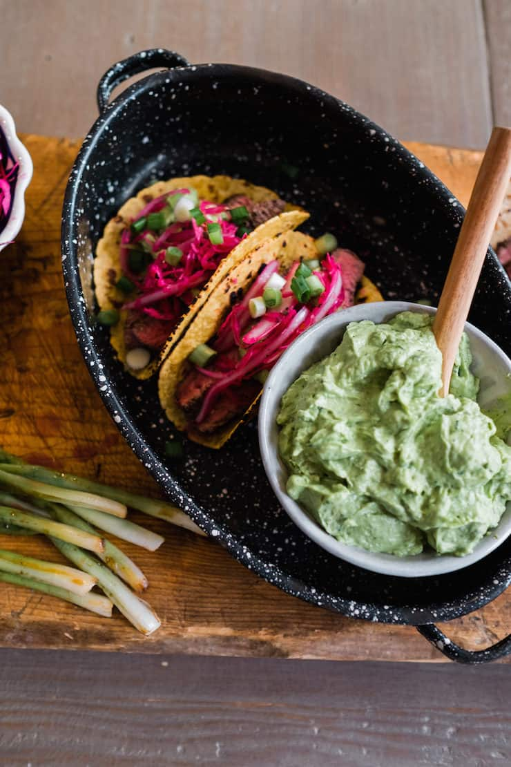 serving platter of bison steak tacos on a wooden cutting board with grilled green onions