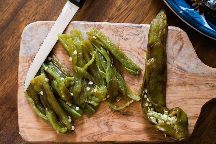 roasted and peeled hatch green chiles on a wooden cutting board