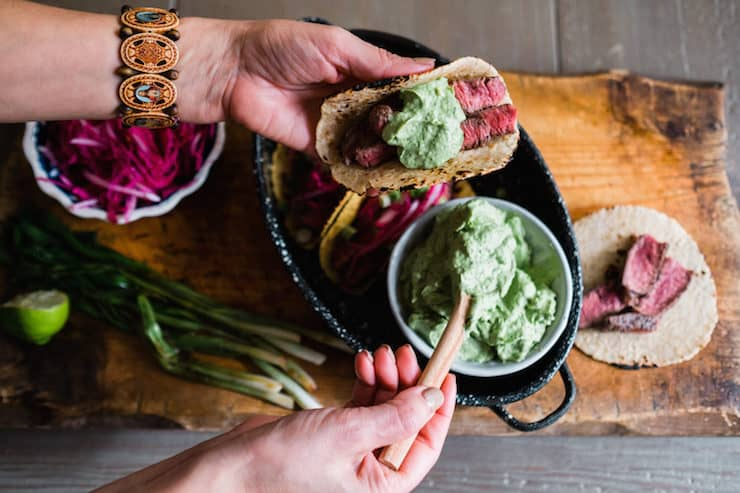 hands assembling a bison steak taco on a corn tortilla with sliced bison and avocado crema