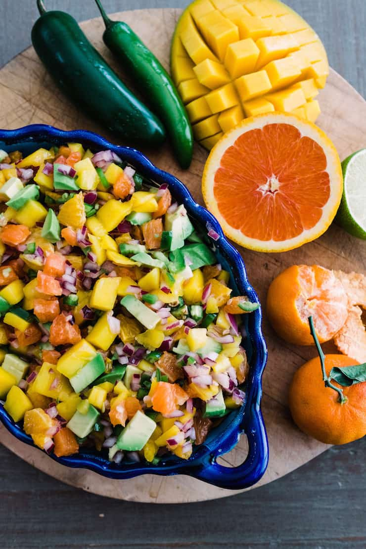 overhead shot of a blue scalloped bowl of orange, avocado and mango salsa on wooden cutting board next to fresh jalapeños, mango, cara cara orange, lime and tangerine