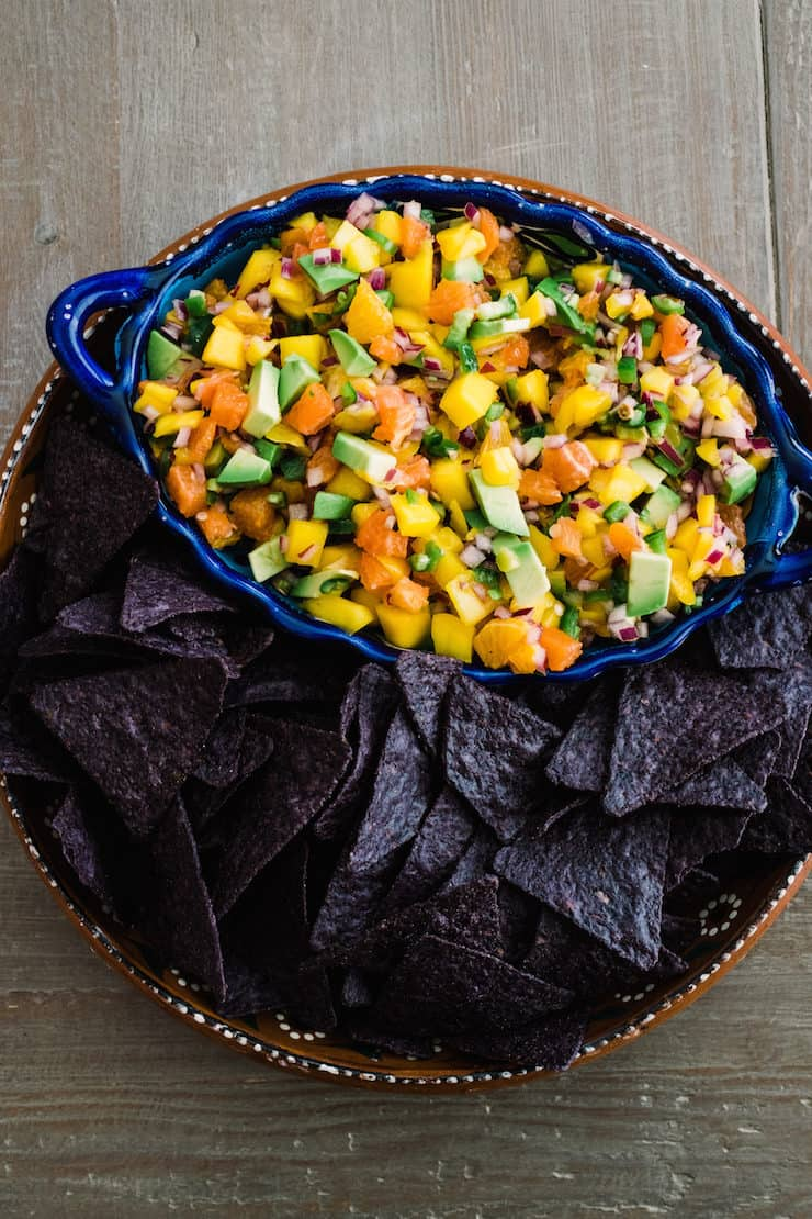 blue serving bowl of orange, avocado and mango salsa on a serving tray filled with blue corn tortilla chips