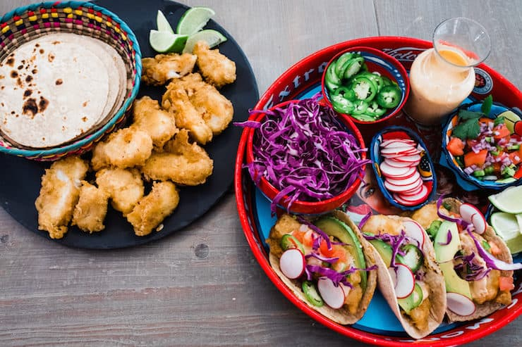 overhead shot of red platter Baja-style fish tacos and black platter of beer battered fried fish with a bowl of chipotle crema