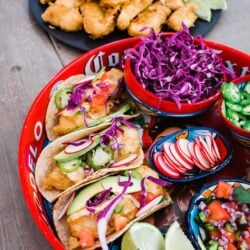beer battered baja fish tacos on a red platter