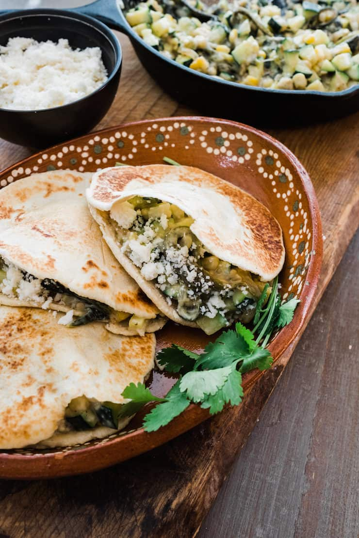 three Gorditas de Harina filled with Creamy Zucchini, Corn, and Poblano Rajas on a Mexican brown plate