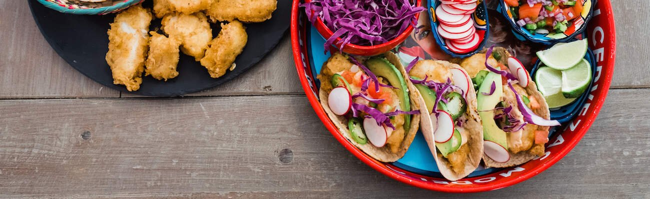 overhead sot of platters filled with baja style fish tacos