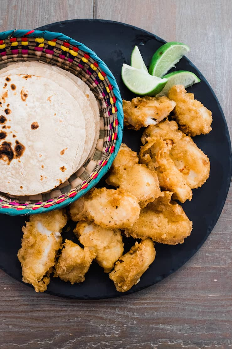 beer battered fried cod on a black serving platter with a side of chipotle crema and lime wedges