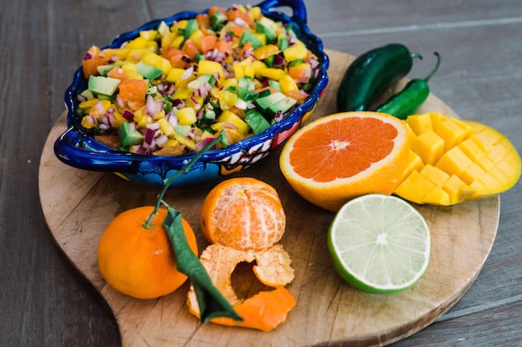 blue bowl of orange, avocado and mango salsa on a cutting board with the raw ingredients to make it