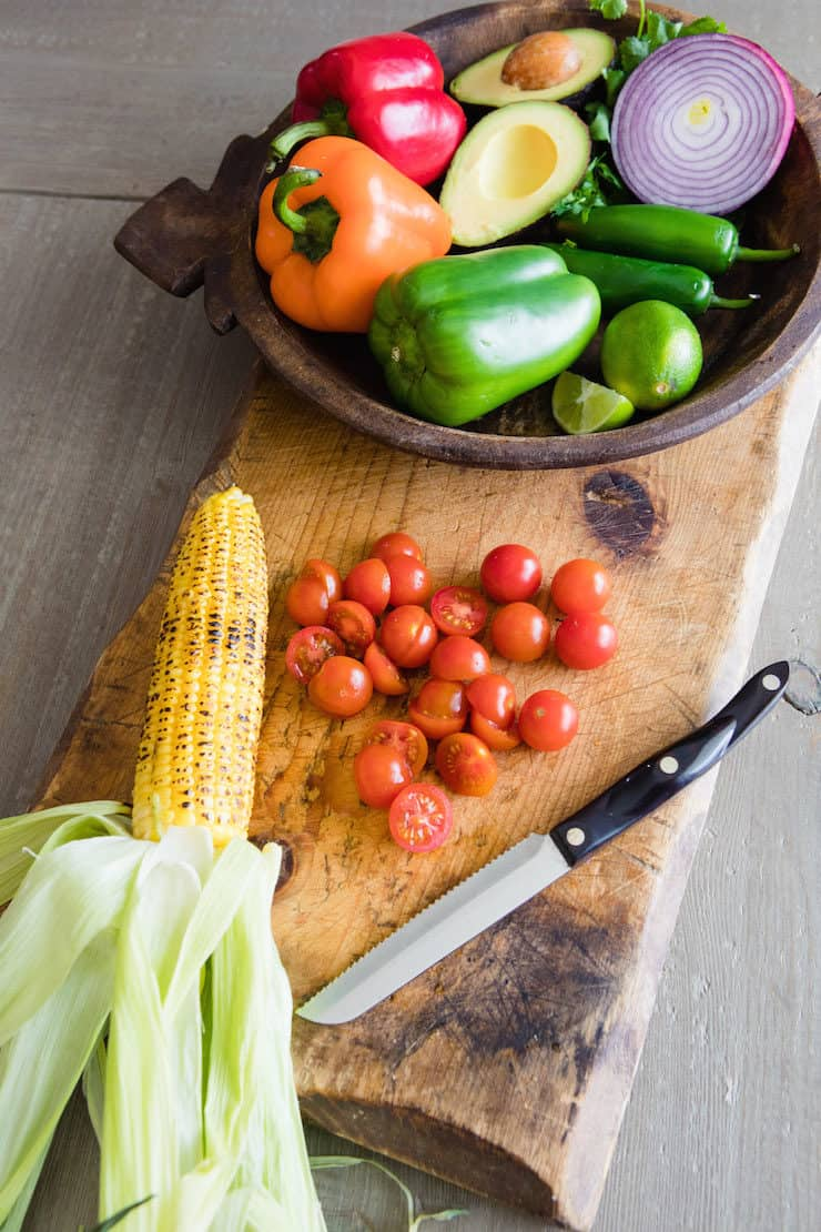 wooden bowl of veggies on a cutting board with an ear of roasted corn and some halved cherry tomatoes
