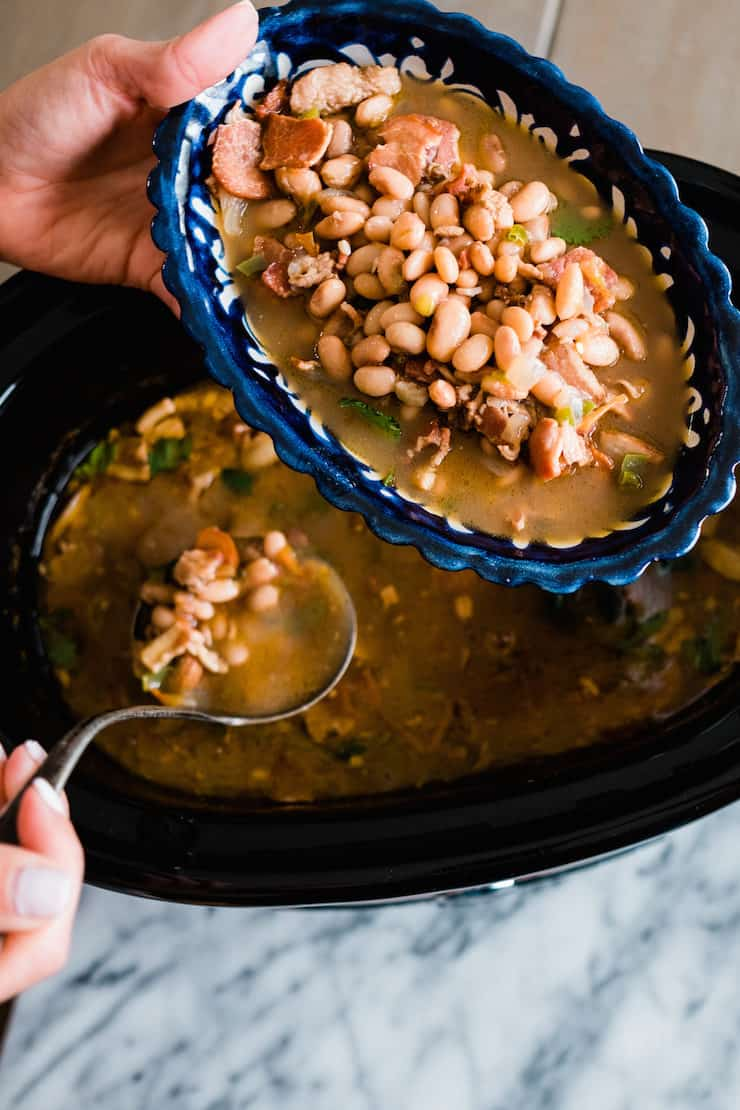 hand ladling borracho beans from slow cooker to blue scalloped serving dish
