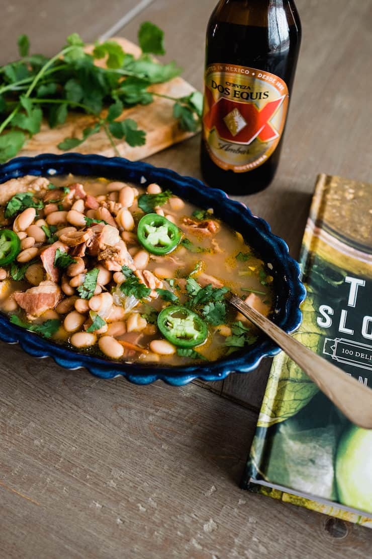 scalloped blue bowl filled with borracho beans on a wood table with a bottle of dos equis beer