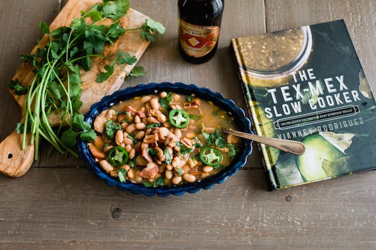 """blue scalloped serving dish of borracho beans next to """"Tex Mex Slow Cooker"""" cookbook, bottle of beer and a wooden cutting board of fresh cilantro"""