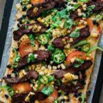 carne asada taco pizza on a baking sheet