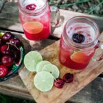 Mason jar mugs filled with Cherry Limeade Margaritas on a cutting board with line slices and bowl of cherries