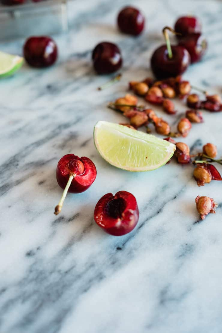 Pitted cherries and juicy lime wedge on a marble counter
