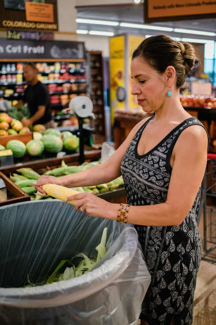 Latina woman shucking corn at King Soopers supermarket